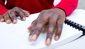 Man getting help reading Braille