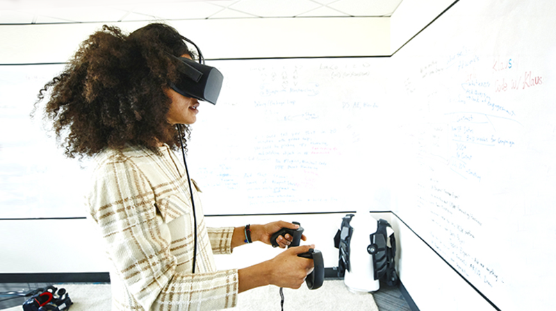 Woman using VR headset and handsets in classroom with whiteboards